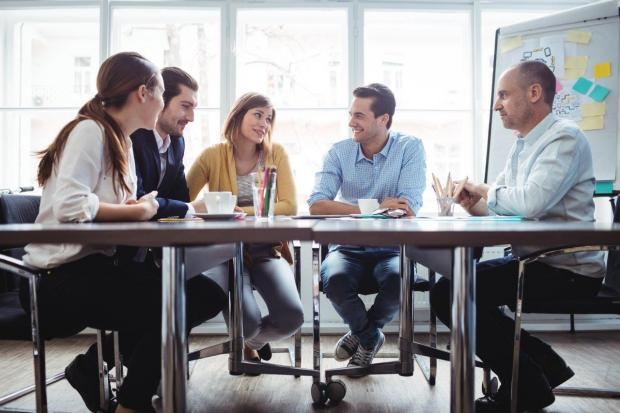 Image of colleagues chatting at a table in front of a whiteboard